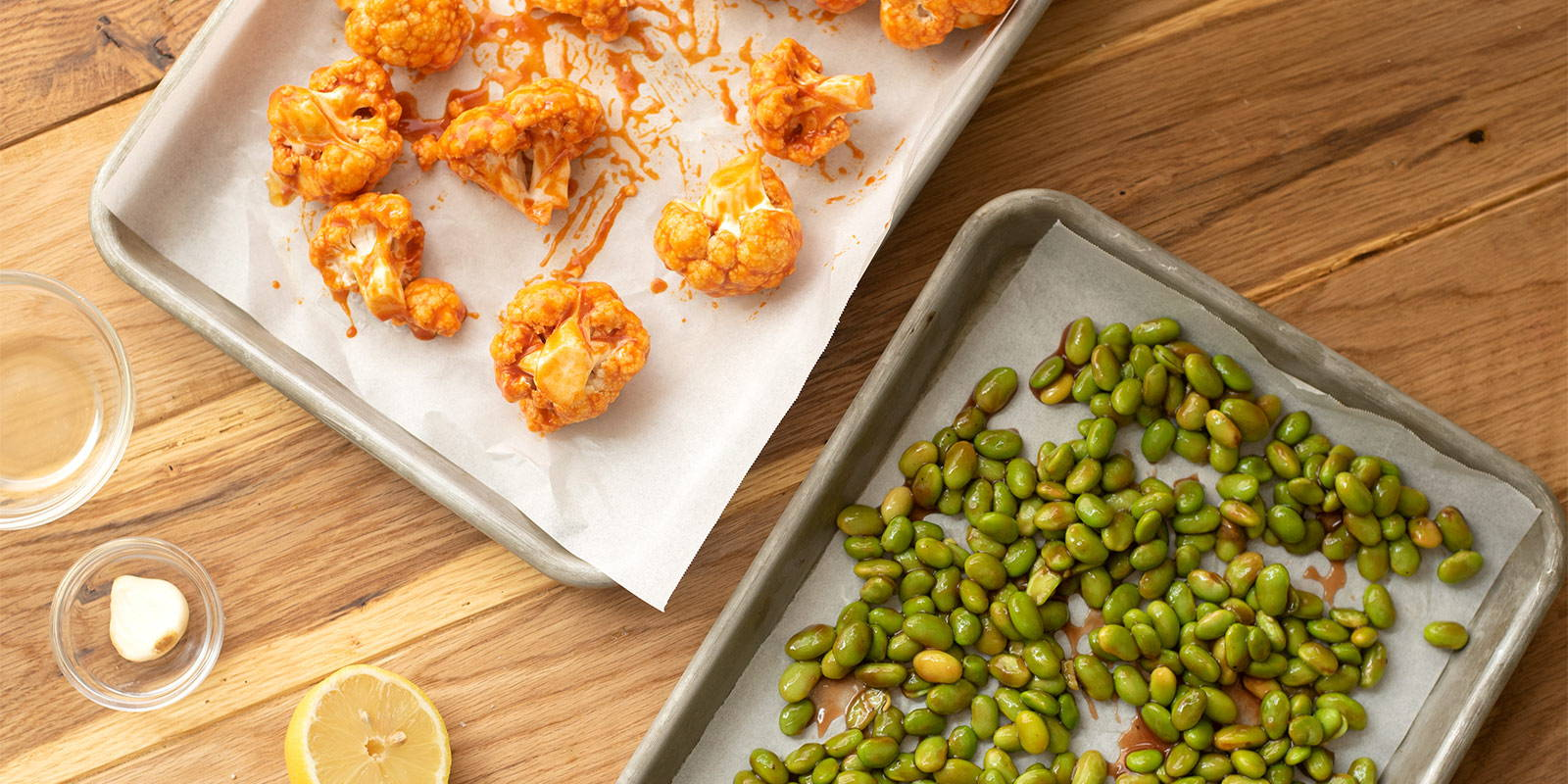 Two parchment paper lined trays, one featuring cauliflower and the other edamame.