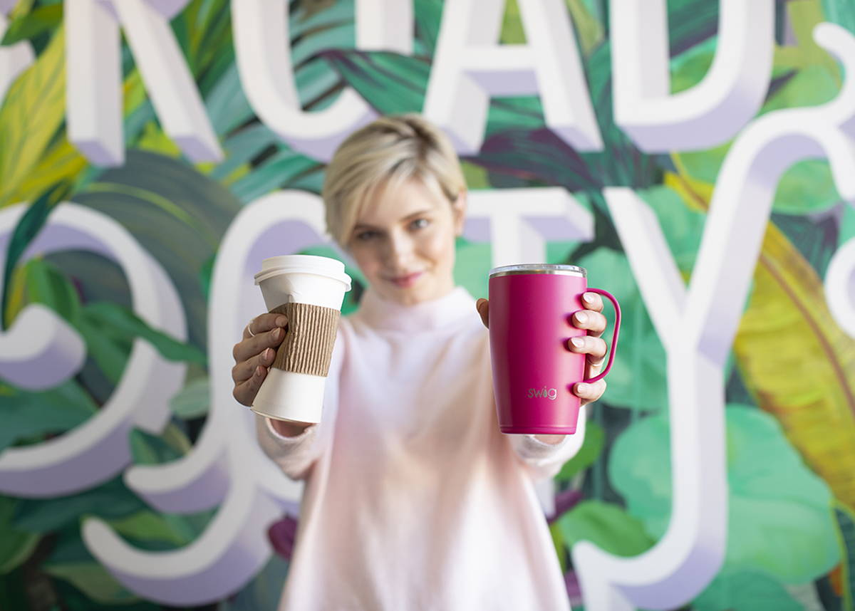 Woman crushing coffee cup while holding pink reusable coffee mug