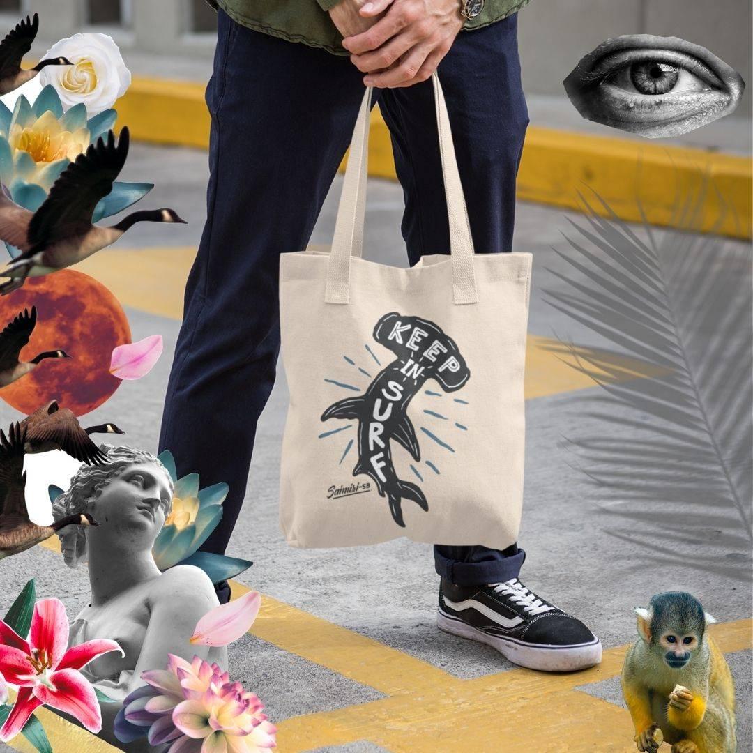 C'est une photo avec un homme dans un skatepark tenant un sac en coton bio. Sur le sac un requin en voie de disparition est dessiné pour sensibiliser le monde à l'écologie. Il est inscrit Goodies. L'homme porte des chaussures de la marque Vans.