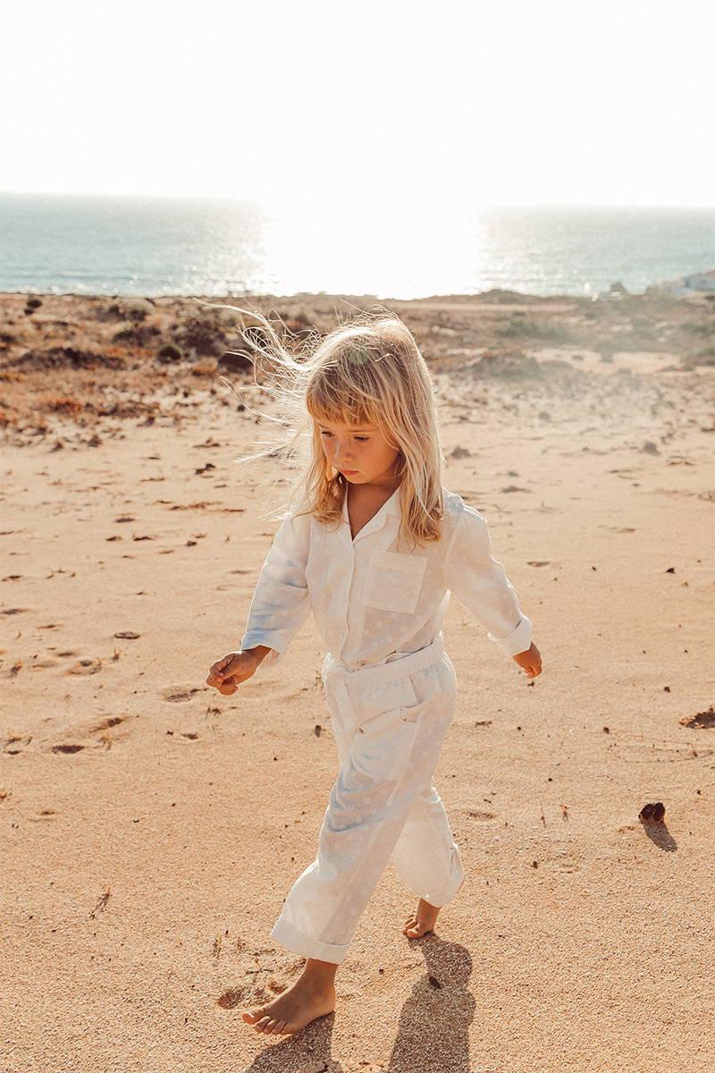 Little girl walking on the beach in her white cotton pyjamas