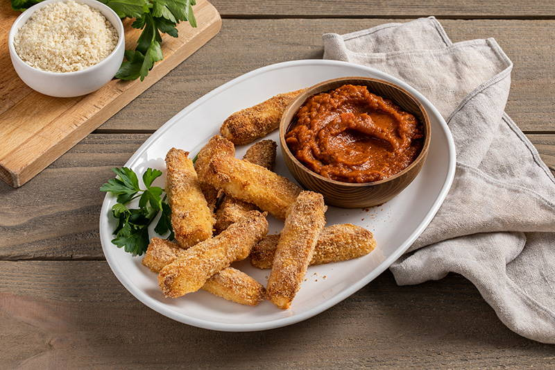 Baked cheese sticks with side of marinara sauce.