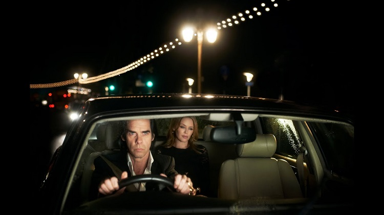 A man driving a car at night with a woman in the back seat