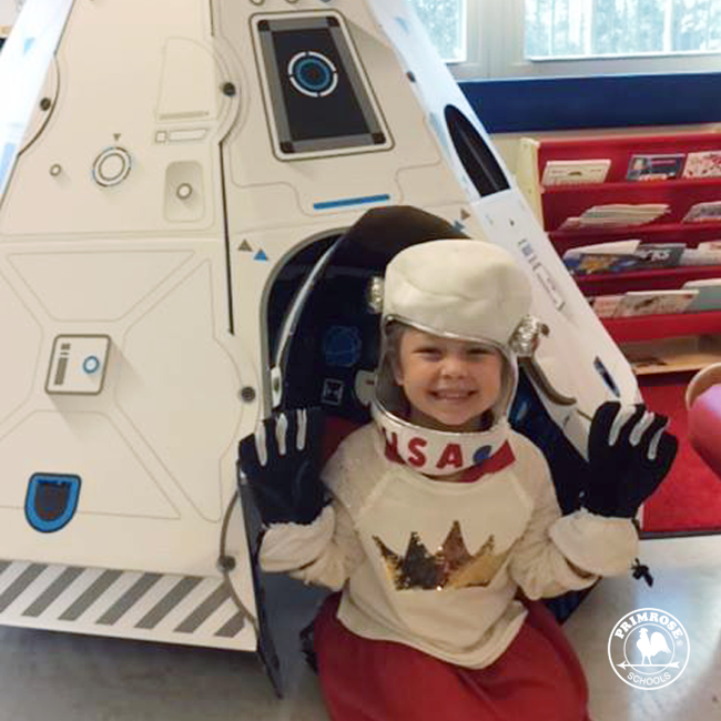 Little girl dressed as an astronaut sits in a play rocket ship