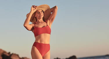 woman in a two-piece bathing suit on the beach wearing a floppy sunhat
