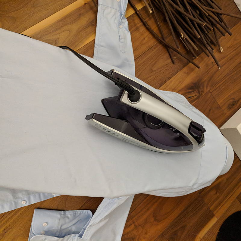 back flap of slim dress shirt over ironing board with iron on top