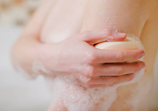Woman under shower using soap