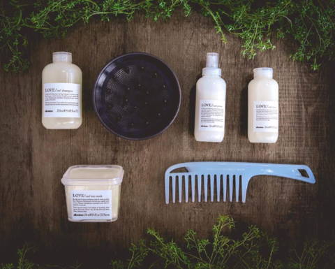 Davines products on a wooden table with a bowl, a comb, and greenery