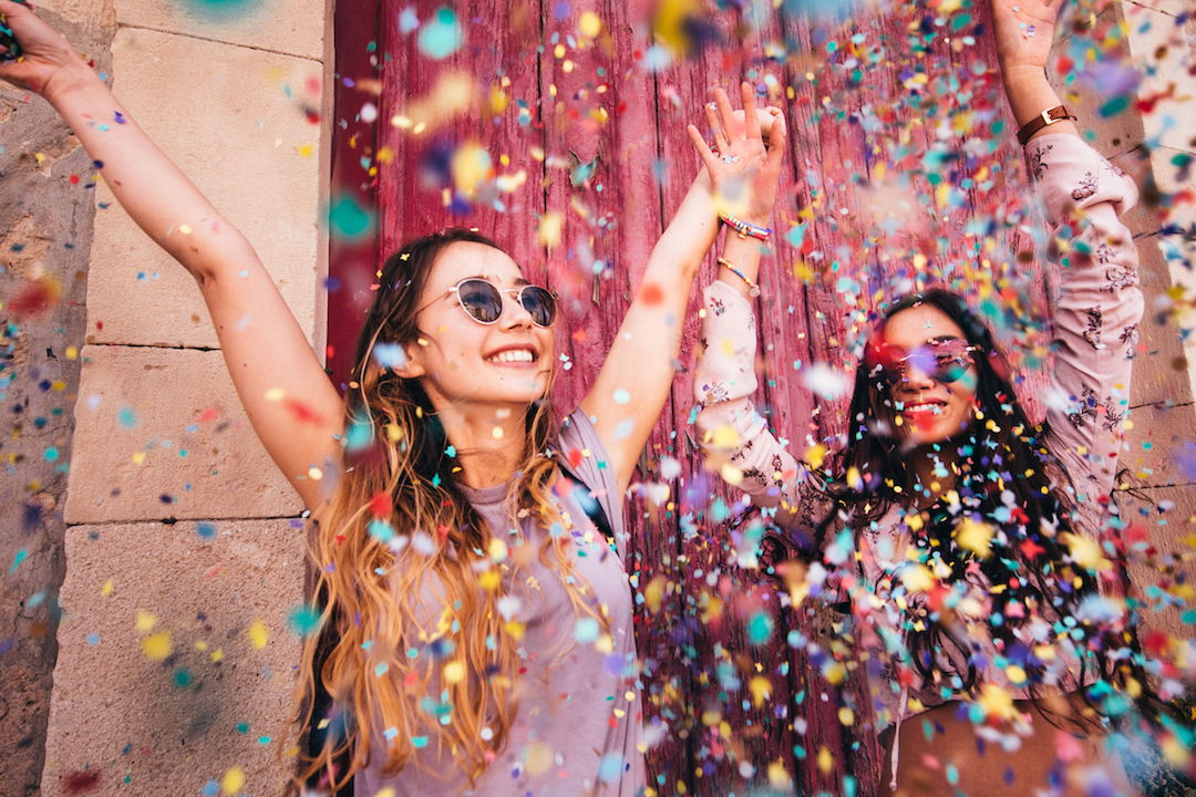Image of two ethnic young women with sunglasses with their hands in the air and a lot of colorful paper and glitter flying everywhere.