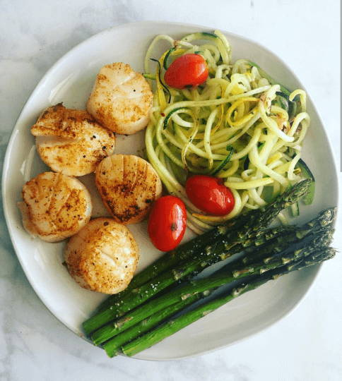 A plate with sautéed scallops, zucchini noodles, cherry tomatoes, and asparagus.