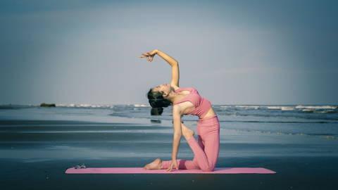 Eine Frau mit pinken Klamotten macht auf einer pinken Yogamatte Yoga