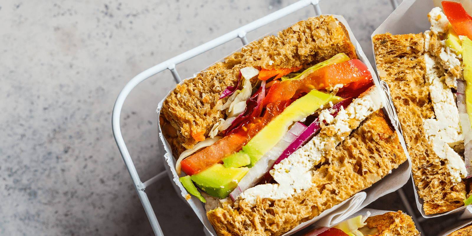 Sandwich cut in half on a platter.