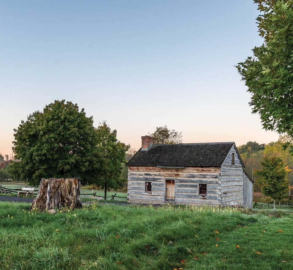 Photograph of a Joseph Smith's family cabin, a small home surrounded by trees and fields.