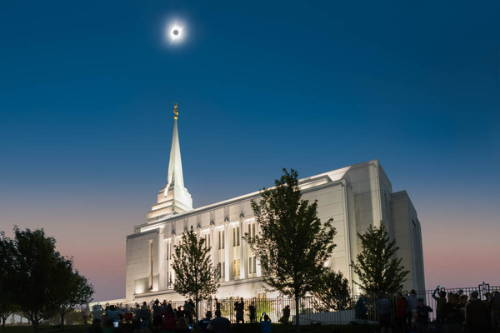 Rexburg LDS Temple picture taken during the eclipse. The eclpised sun hangs directly above the steeple.