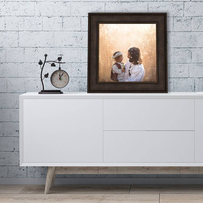 Image of Jesus holding a child. Painting is placed on a low table next to an artistic clock that matches the painting's frame.