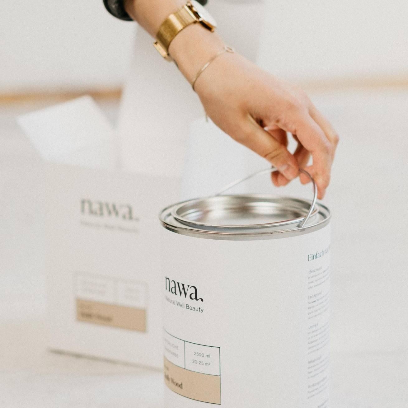 nawa wandfarben farbeimer mit produktverpackung und hand