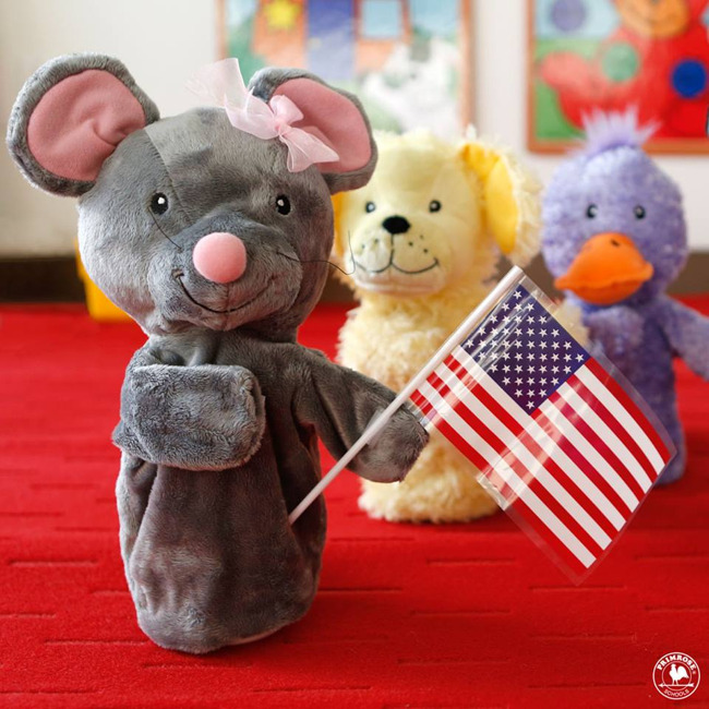 Primrose puppet Mia the mouse stands with an American flag while other puppets look on