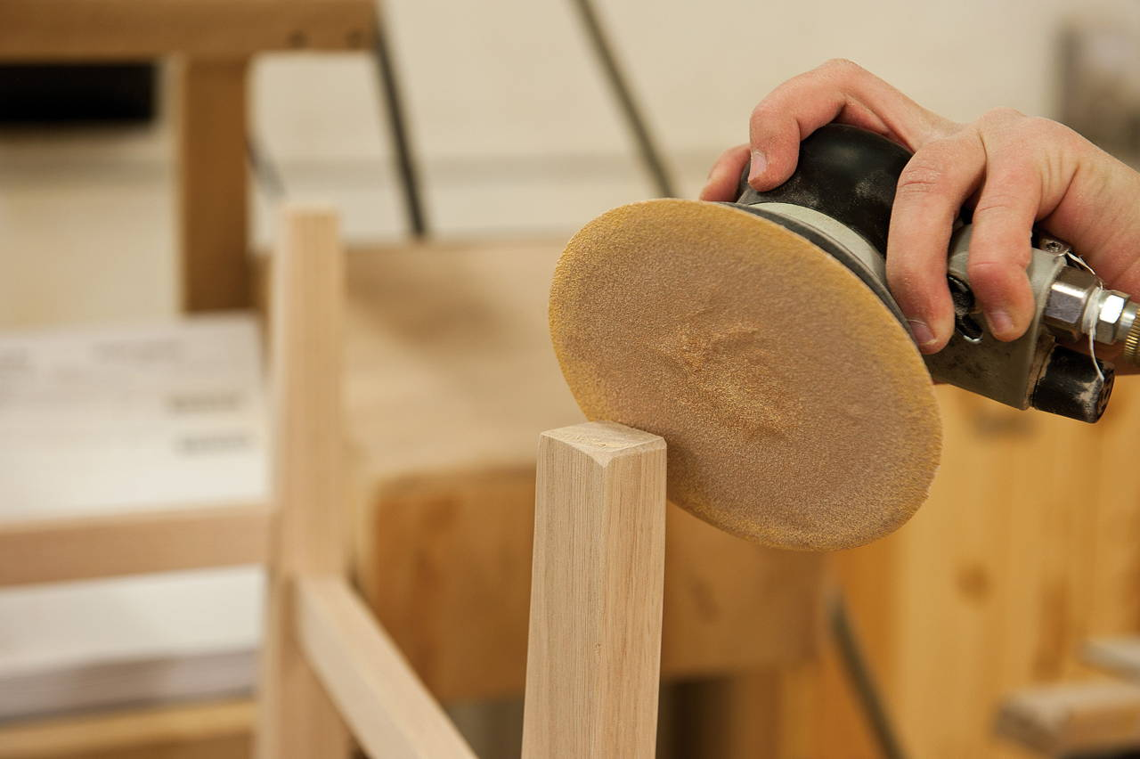 Amish craftsman sanding a wood chair