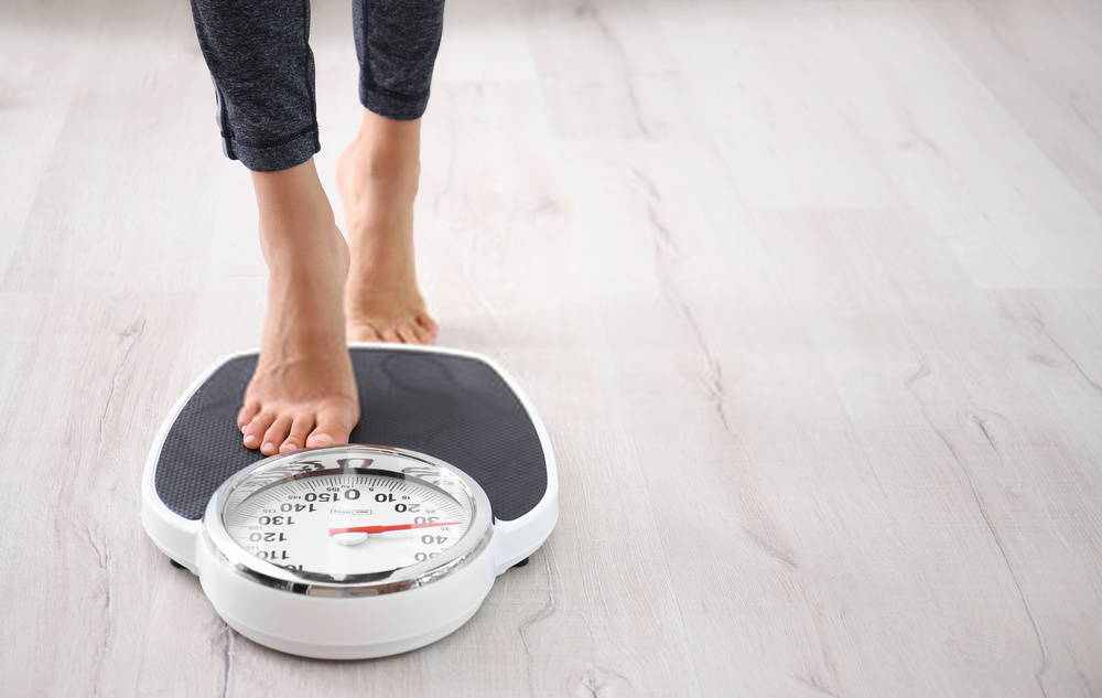 woman stepping onto bathroom scale