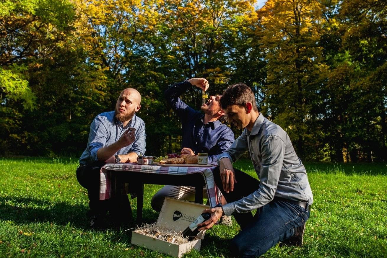 3 Männer am Tisch mit gudBox in der Natur