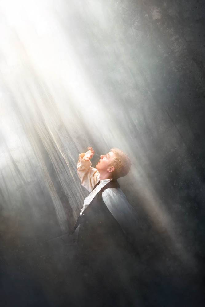 Photo art of Joseph Smith's First Vision. He is kneeling in darkness, shielding his eyes from a great light shining down on him.