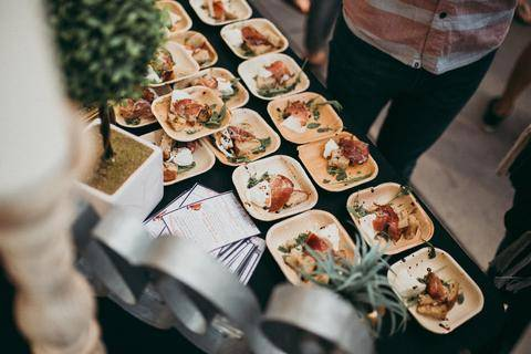 many plates being filled with food on a table