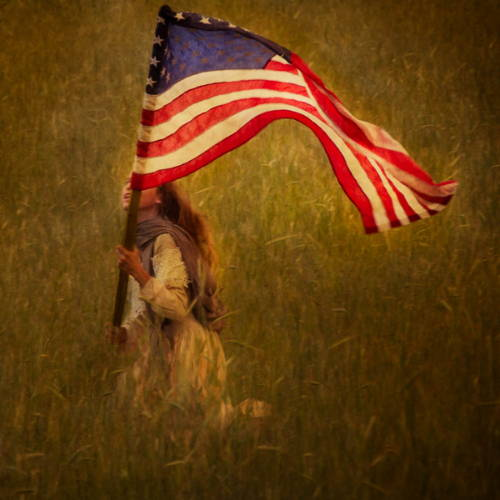 Little girl happily running through the field with an American flag.
