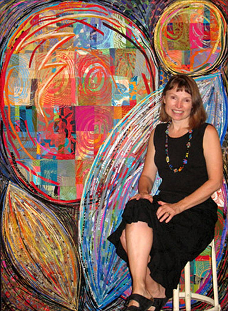 Sue Benner next to one of her quilted artworks