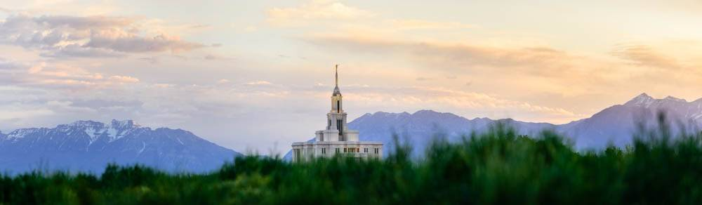 Panoramic photo of the Payson Temple against a landscape of blue mountains.