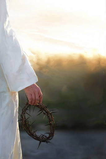Jesus' hand holding a crown of thorns.