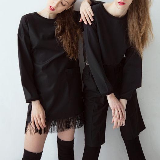 Черное платье с карманом и бахромой.
