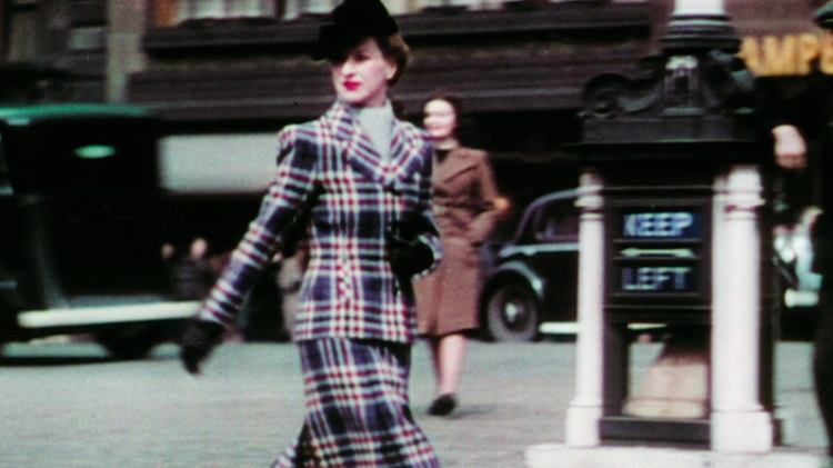 A woman in a tweed skirt suit crosses the road.