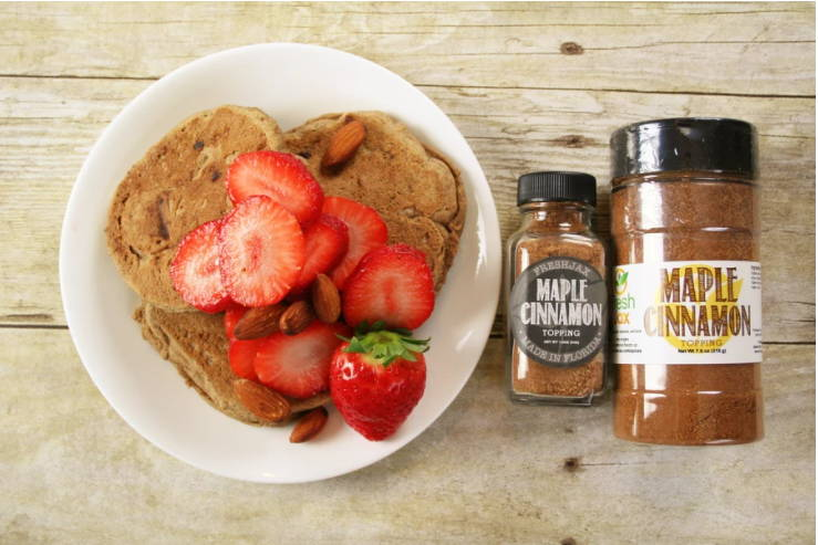 A plate filled with pancakes topped with strawberries and almonds next to a sampler and large bottle of FreshJax Organic Maple Cinnamon Topping.
