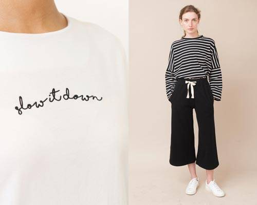 Woman wearing organic cotton slow it down slow fashion slogan tee and woman wearing striped organic long sleeve tee with black wide leg organic cotton jersey trousers