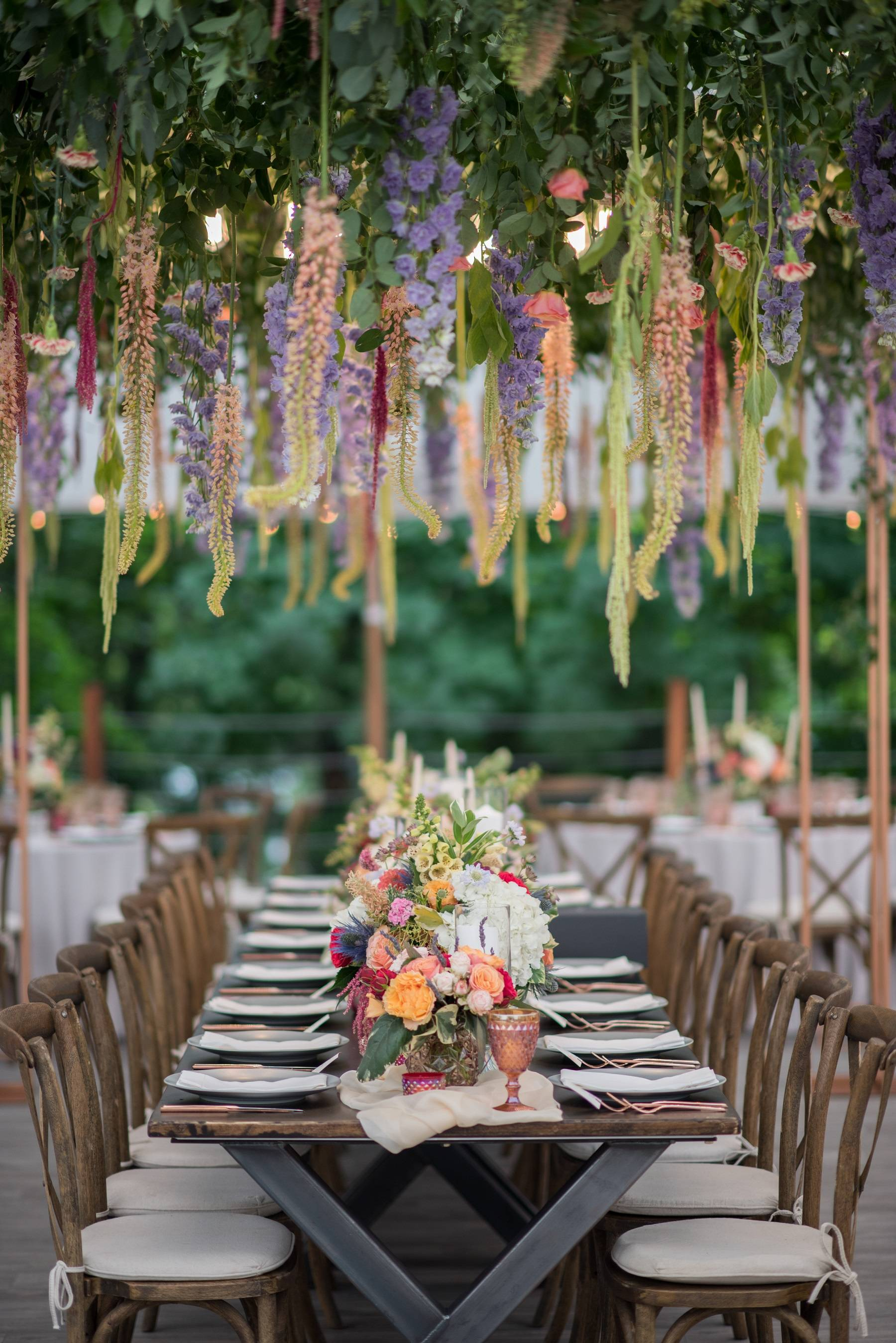 McCarthy Rentals Farm Table with a long colorful centerpiece.  Head table with hanging floral