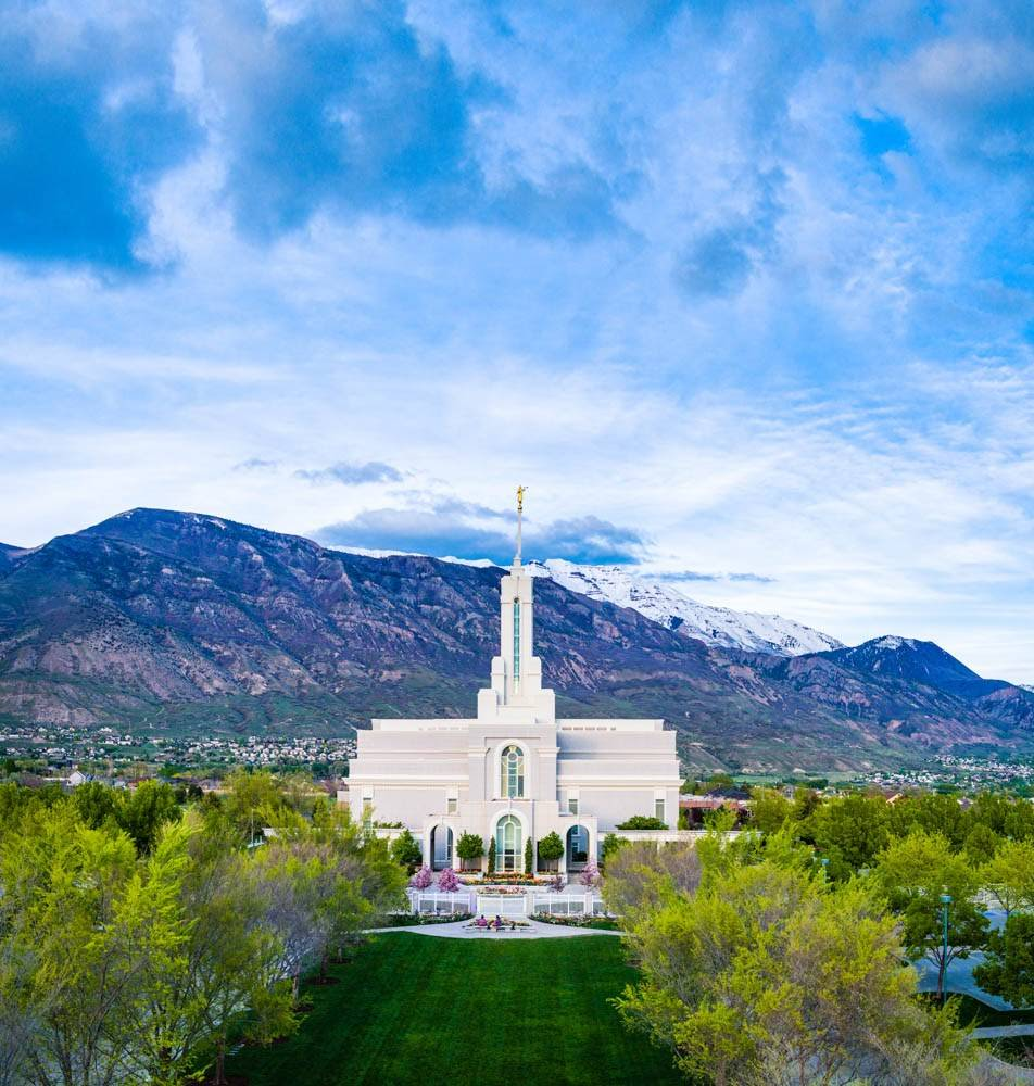 Vertical LDS photo of Mount Timpanogos Temple against a blue sky and mountains.