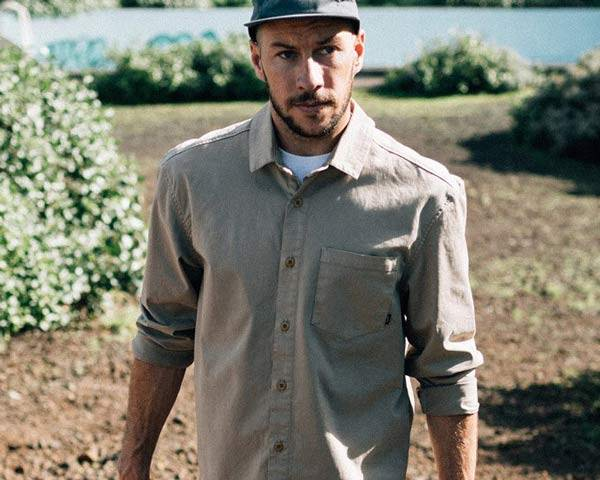 Man wearing grey finisterre organic cotton shirt with 5 panel cap and white undershirt in the countryside