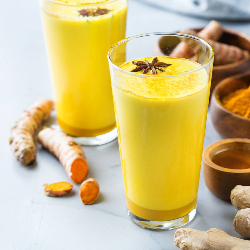 Glass of turmeric shake with turmeric root next to it