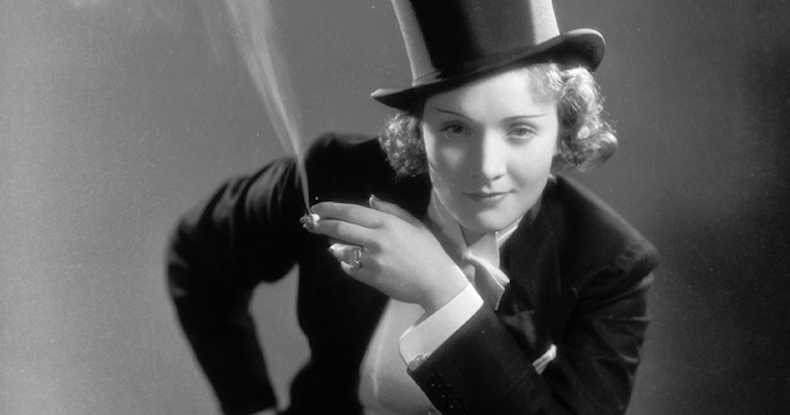 Image of Marlene Dietrich in her signature suit, and a cigarette in her hand, smirking at the camera.