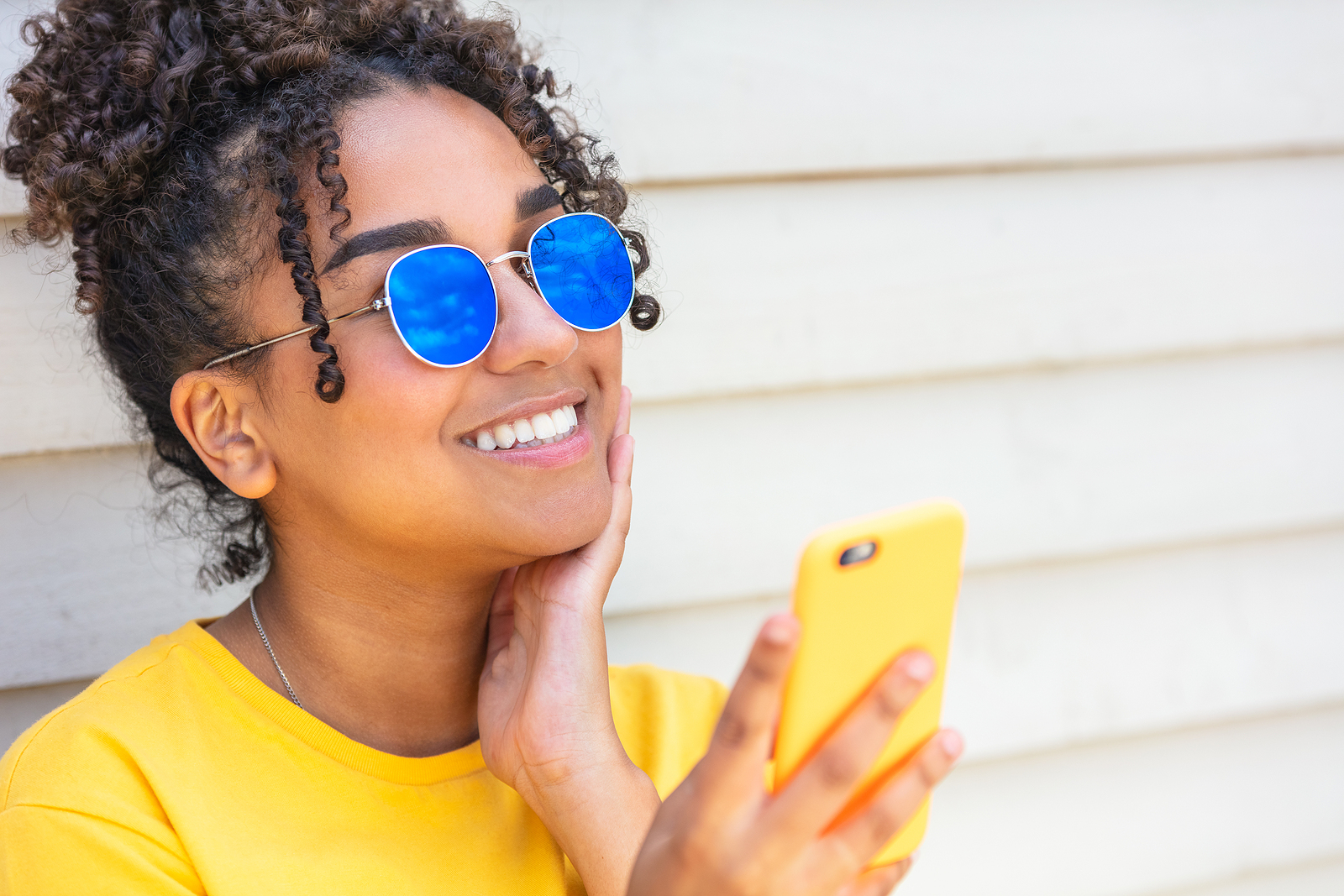 An attractive black woman with sunglasses hold her phone up and smiles for the camera.