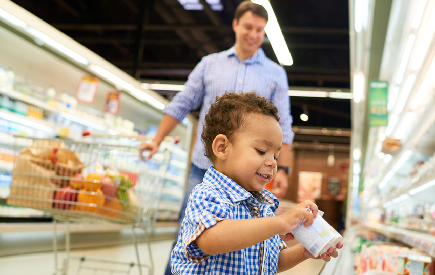 Little toddler boy picks up a pack of yogurt in the supermarket as his father looks on