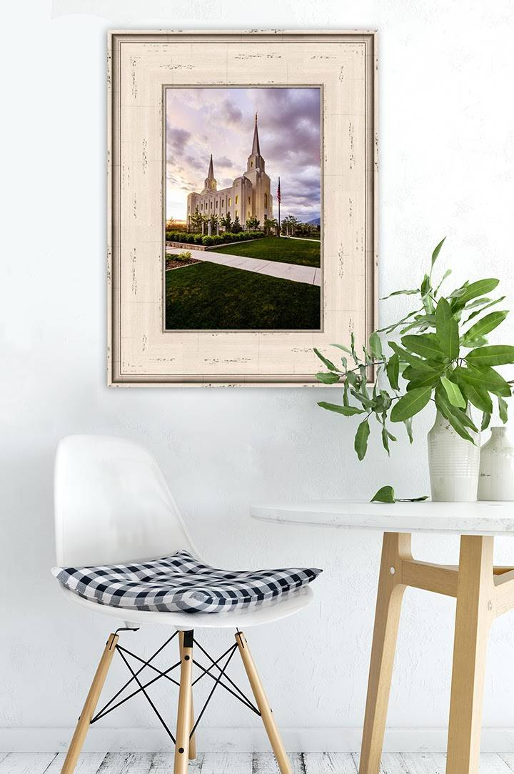Vertical painting of the Brigham City Temple placed on the wall above a small chair and a table with potted plants.