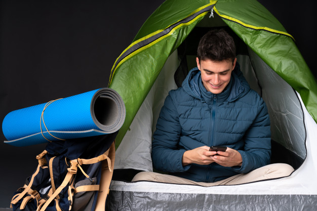 Teenager caucasian man inside camping green tent isolated black background sending message with mobile 1368 117459