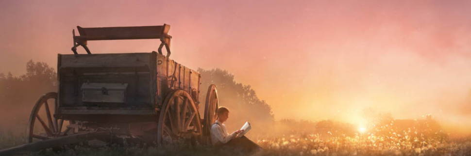 LDS art picture of Joseph Smith sitting in a field against a wagon reading the Bible.