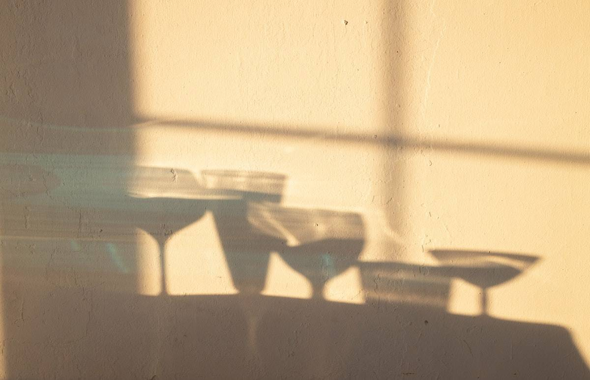 Shadow of various wine glasses on a blank wall .