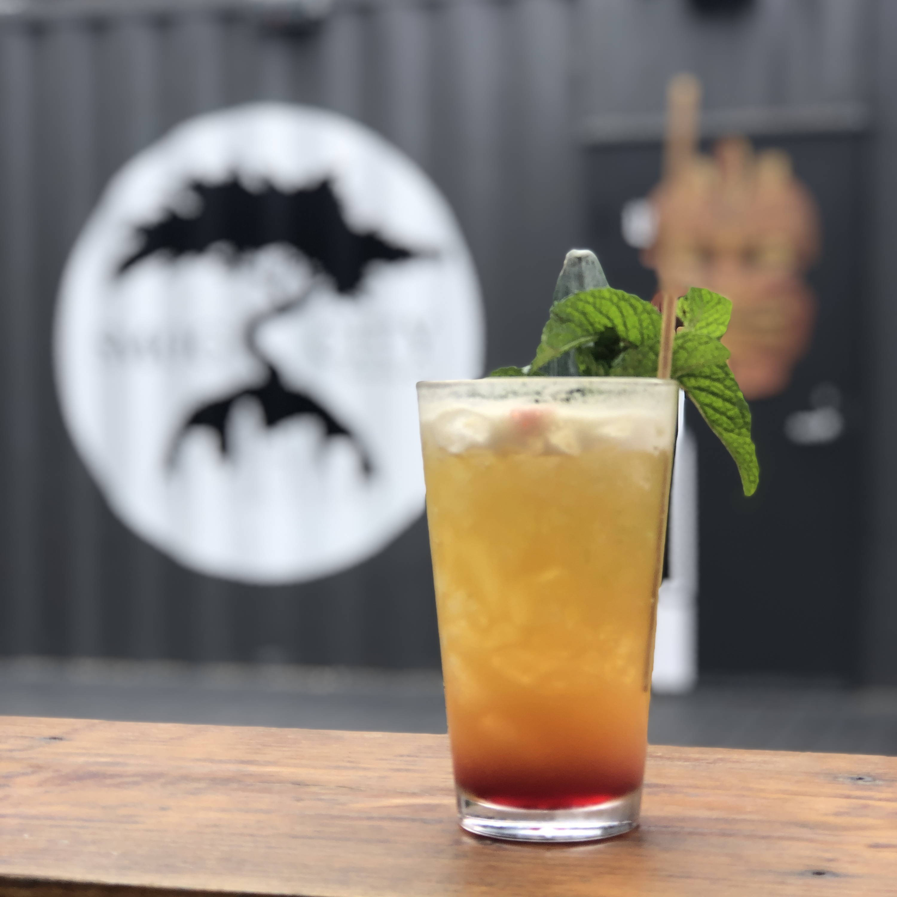 the MSog city logo can be seen in the background behind a tropical and refreshing looking cocktail.