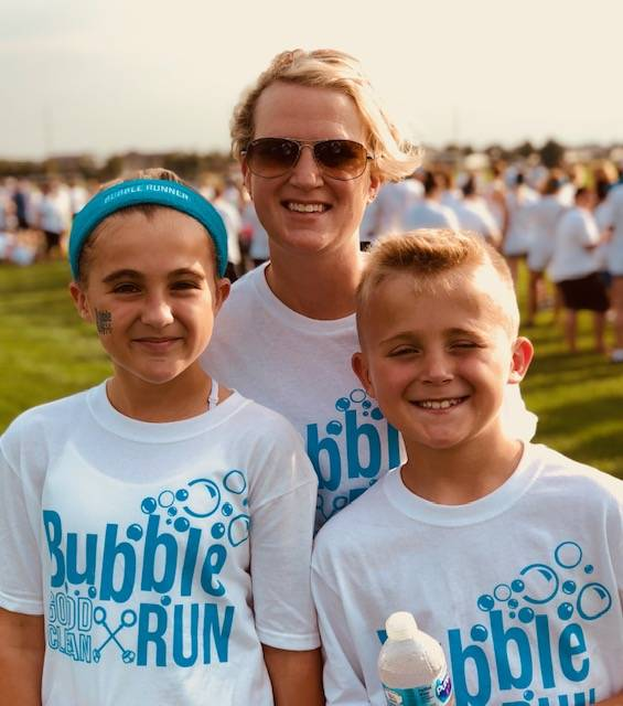 """A photo of Rachael Masters with her two kids (a pre-teen daughter and elementary-aged son). They are at the""""Bubble Run"""" on a sunny day."""