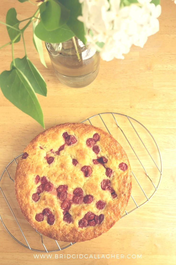 Cherry-Studded French Yogurt Cake recipe - photo of a cake on a cooling rack with a vase of lilacs in the background \\ full recipe on www.bridgidgallagher.com