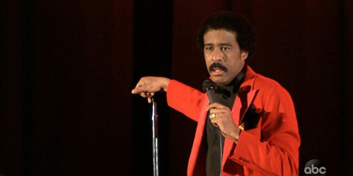 Richard Pryor in a red jacket standing at a microphone on a dark stage.