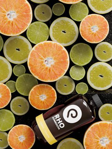 Rho Kombucha mit der Geschmacksrichtung Ingwer/Limette welche von Limetten und Orangen umgeben ist