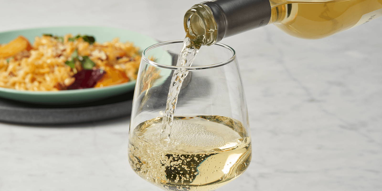 Pouring white wine into a glass.